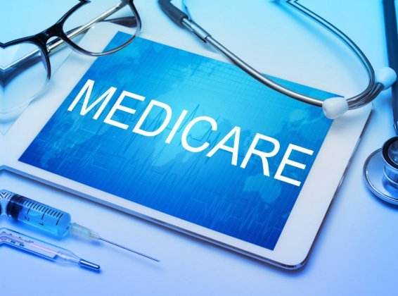 Medicare word on tablet screen with medical equipment